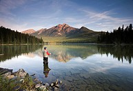 Middle aged male fly fishing in Pyramid Lake, Jasper National Park, Alberta, Canada