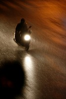 fast motorbike rider heavy rain at night in town