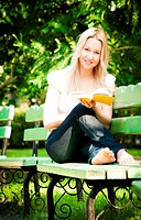 young woman sitting on bench in park, reading book, smiling and looking into the camera
