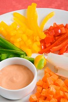 An appetizer plate with sliced vegetables and a cup of tomato mayonnaise shallow DOF _ focus on the sauce cup