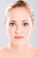 attractive caucasian woman face marked with lines for cosmetic surgery