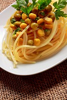 Spaghetti with green peas preserved, sweetcorn and parsley leaves on plate