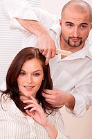 Professional male hairdresser comb female customer at salon