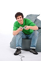 Young happy man playing video game with control pad on white background