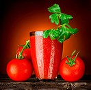 A wet glass of tomato juice decorated with parsley and ripe tomato bunch on a wooden table.