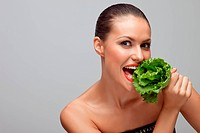A hot sexy lady biting green lettuce.