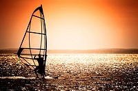 windsurfer silhouette against a sunset background