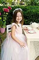 A cute little girl having a pretend tea party outside in the garden, selective focus