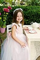 A cute little girl having a pretend tea party outside in the garden, selective focus