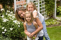 Mother and her two daughters in a garden, Ontario, Canada