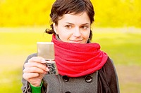 Girl with red scarf looks in mirror against autumn.