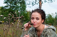 beauty girl sit on meadow near burdock on the trees background