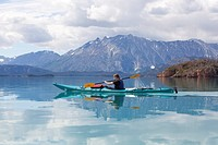 Young woman in a sea kayak, paddling, sea kayaking, mountains behind, Tagish Highland, Mount Fetterly, Atlin Lake, British Columbia, Canada, America