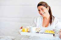 Beautiful happy woman having breakfast in bed