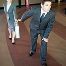 Businesswoman passes a briefcase off to a businessman in place of a relay baton.
