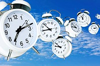 composite image of several alarm clocks with varying hand positions flying through blue sky