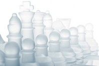 glass chess pieces are standing on board, cut out from white background