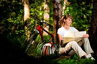 beautiful young woman sitting near her bicycle under the tree in forest with map in her hands