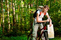 beautiful young woman sitting on her bicycle with bottle of water in hand and map in the middle of summer forest