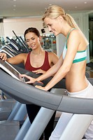Woman Working With Female Personal Trainer On Running Machine In Gym
