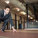 Businessman ready to sprint on an indoor track.