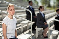 Beautiful spectator sitting on bleachers with businesspeople in the background.