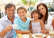 Young Family Enjoying Cup Of Coffee And Cake In CafŽ Together