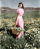 Rear view of a girl standing in a meadow holding a flower basket and smiling All persons depicted are not longer living and no estate exists. Supplier...