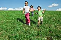 Kids playing on a grassy slope in Italy