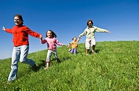 Family running down with joy on a grassy hill in Nova Ponente, Alto Adige, Italy