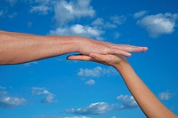 Two Hands Touching Against Blue Sky