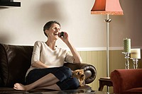 Senior woman sitting on sofa talking on telephone