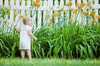Caucasian girl exploring flowers in backyard