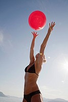 Caucasian woman in bikini catching ball