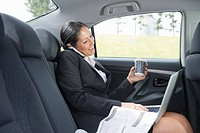 Hispanic businesswoman using cell phone and laptop in back of car