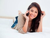 A woman holding her hair and making a call as she lies on the bed, while smiling and looking forward