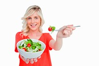 White bowl of vegetable salad held by a young woman against a white background