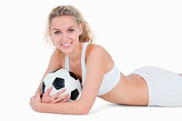 Smiling teenager lying down with a football in her arms against a white background