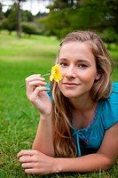 Young relaxed woman holding a beautiful yellow flower while lying in the countryside