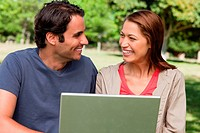 Two friends joyfully smiling as they look at each other while holding a tablet in a park on a sunny day