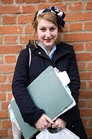 portrait of teenage school girl with her art folders standing against brick wall