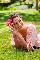 Smiling woman with her head tilted to the side lying on the grass while holding a pink flower against her head