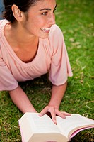 Woman looking towards the side while reading a book as she is lying down in grass
