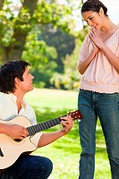 Woman standing and smiling with her hands joined as she admires her friend who is playing the guitar