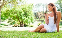 Young woman sitting on the lawn while smelling a flower