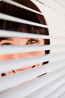 A woman smiling as she glances into the camera through some blinds