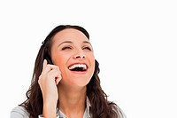 Brunette laughing while making a call against white background
