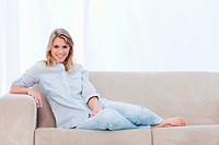 A blonde smiling woman sitting on a couch is looking at the camera