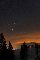 Alpine night sky. Starry winter night in Carinthia, Austria. Trees, snow and a lodge are in the foreground. In the distance, the light seen above the ...
