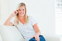 A smiling woman talking on her phone while looking at the camera as she sits on the couch